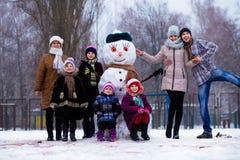 Zeer grote familie van drie generaties: de grootmoeder, de vader, de moeder en de dochters beeldhouwen grote echte sneeuwman Gelu royalty-vrije stock afbeeldingen