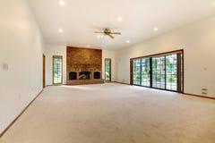 Zeer grote lege woonkamer met baksteenopen haard. Royalty-vrije Stock Fotografie