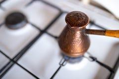 Zeer hete klaar koffiehoed - Koffie die in een koper cezve op een gasfornuis in comfortabele typische keuken in de ochtend wordt  stock foto