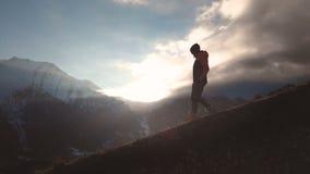 Zeer lang geschoten Satellietbeeld van een episch schot van een meisje die op de rand van een berg als silhouet in mooi lopen stock footage