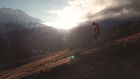 Zeer lang geschoten Satellietbeeld van een episch schot van een meisje die op de rand van een berg als silhouet in mooi lopen stock videobeelden