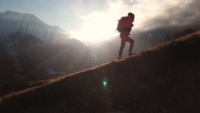 Zeer lang geschoten Satellietbeeld van episch schot van een meisje die op de rand van de berg als silhouet in mooi lopen stock video