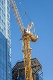 Zeer lange bouwkraan naast wolkenkrabber Stock Afbeeldingen