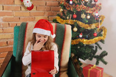 Zeer leuk babymeisje met weinig rode doos in handen op de stoel dichtbij Kerstboom Royalty-vrije Stock Afbeelding