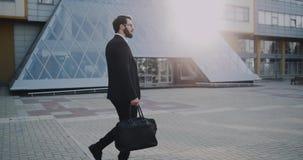 Zeer modieuze jonge mens in een kostuum met zwarte zonnebril die onderaan het moderne commerciële centrum lopen stock videobeelden