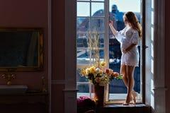 Zeer mooi zwanger meisje met schitterend haar in een witte kleding stock afbeelding