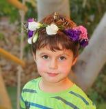 Zeer mooie die jongen met een kroon van bloemen wordt bekroond stock fotografie