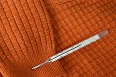 Zeer op hoge temperatuur Wijzend op een hoge koorts Op een sweater breiende sinaasappel Royalty-vrije Stock Fotografie