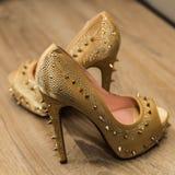 Zeer originele gehielde schoenen in goud met een decoratie van spijkers op een parketvloer royalty-vrije stock foto's