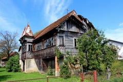 Zeer oud gebroken die blokhuis in groene installaties wordt behandeld Royalty-vrije Stock Foto
