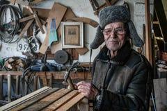 Zeer oude mensenmeester in grijze warme kleren en oogglazen met hamer in handen royalty-vrije stock fotografie