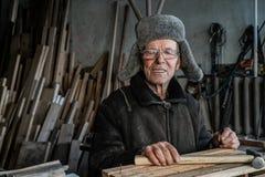 Zeer oude mensenmeester in grijze warme kleren en oogglazen met hamer in handen royalty-vrije stock afbeelding