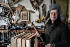 Zeer oude mensenmeester in grijze warme kleren en oogglazen met hamer in handen stock fotografie
