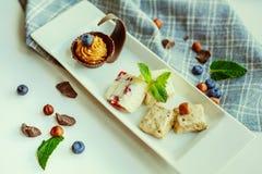 Zeer smakelijke dessert verschillende stukken van cake met de bessen van chocoladenoten en verschillende room Stock Afbeelding