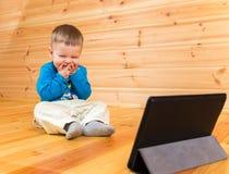 Zeer tevreden weinig jongen die lettend op zijn tabletcomputer genieten van Royalty-vrije Stock Foto