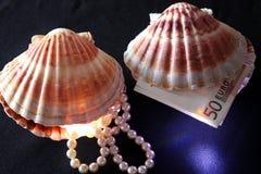 Zeeschelpen met parels en geld Stock Afbeelding