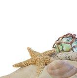 Zeeschelpen op zand met glasbal op wit Stock Foto's