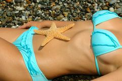 Zeester op een maag bij de vrouw in bikini Stock Foto's