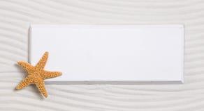 Zeester op een wit teken op een zandachtergrond voor de zomer Stock Afbeelding