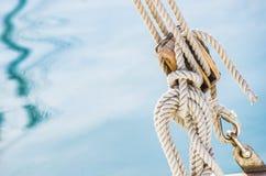 Zeevaart maritieme achtergrond, zeilboot houten katrol met kabels en zeewaterachtergrond stock foto