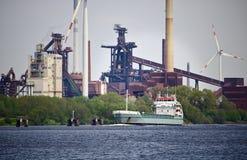 Zeevrachtschip op een rivier met groen gebladerte, reusachtige staalfabriek en verscheidene windenergieposten op de achtergrond Stock Fotografie