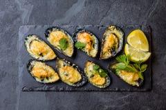 Zeevruchten Gebakken mosselen met kaas en citroen in shells stock foto's