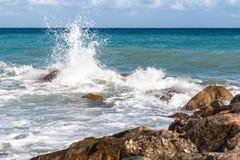 Zeewater dat onderbrekingen op de rotsen stock afbeelding