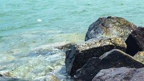 Zeewatergolven en grote stenen op kust Blauw en transparant water op oceaan rotsachtige strandachtergrond Overzeese golven op rot stock videobeelden