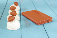 Zefier met rode fonkelende harten met rode notitieboekjeagenda dichtbij op houten planken Royalty-vrije Stock Foto
