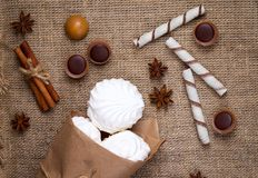 Zefir, sweet wafers rolls and caramel candies on a burlap Royalty Free Stock Photos