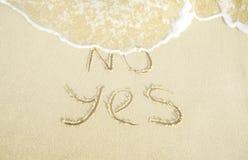 Zeg ja aan het leven Nr en ja woorden op het zand wordt geschreven waar Geen door de golf die gereinigd wordt stock foto's