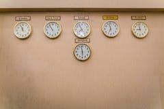 Zegarów przedstawień różne strefy czasowe na starej ścianie Zdjęcia Stock