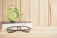 Zegar, eyeglasses i słownik na drewnianym stole, zdjęcie stock