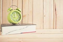 Zegar i słownik na drewnianym stole nad drewnianym tłem zdjęcia royalty free