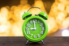 Zegar na Drewnianej podłoga z Żółtym Bokeh tłem Zdjęcia Stock