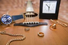 Zegarki, złociści pierścionki, bransoletki i gitara, Obrazy Stock