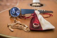 Zegarki, złocisty pierścionek, bransoletki i gitara, Obraz Royalty Free