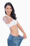 Zegevierende vrouw die haar te grote broek houden en bij c wijzen op stock foto