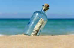 Zehn Dollarschein in einer Flasche auf dem Strand Lizenzfreie Stockbilder
