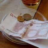 Zehn Euro Bill mit Münzen auf Platte auf Holztisch im Restaurant Lizenzfreie Stockfotografie