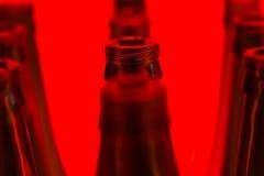 Zehn grüne Flaschen in drei Reihen schossen mit rotem Licht Lizenzfreies Stockbild