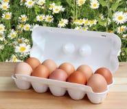Zehn Hühnereien in einem weißen Paket auf dem Tisch Stockbild