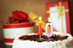 Zehn Jahre Geburtstag Kuchen mit brennenden Kerzen und Geschenken Stockfotografie