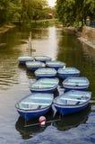 Zehn Ruderboote auf ruhigem Kanal Stockfoto