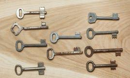 Zehn symmetrisch vereinbarte Schlüssel auf einem hölzernen Hintergrund stockbild