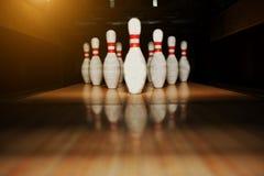 Zehn weiße Stifte in einem Bowlingbahnweg lizenzfreie stockfotografie