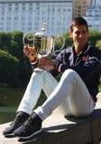 Zehnmal Grand Slam-Meister Novak Djokovic, das im Central Park mit Meisterschaftstrophäe aufwirft lizenzfreies stockfoto