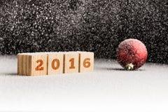 Zeichen 2016 auf hölzernen Würfeln und roten dem Weihnachtsball, die auf einem Schnee liegt Lizenzfreie Stockbilder