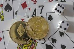 Zeichen Bitcoin und des etherium mit Karten und Würfeln Lizenzfreie Stockfotos