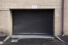 Zeichen CCTV in Kraft über großem schwarzem Garagentorfensterladen lizenzfreie stockfotos